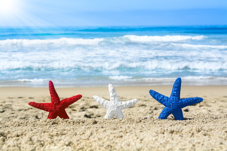 Photo pour Conceptual summer holiday image of three red, white and blue starfish on the beach overlooking a turquoise ocean while celebrating the July fourth holiday. - image libre de droit