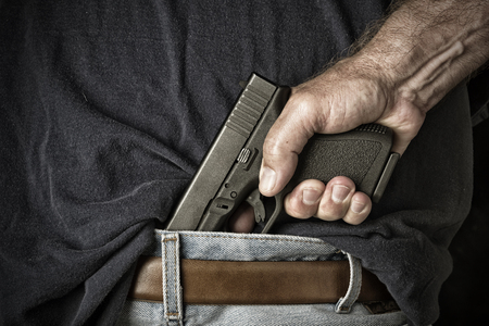 Photo for A man with a pistol in his waistband grasps the handle in preparation for pulling the weapon - Royalty Free Image