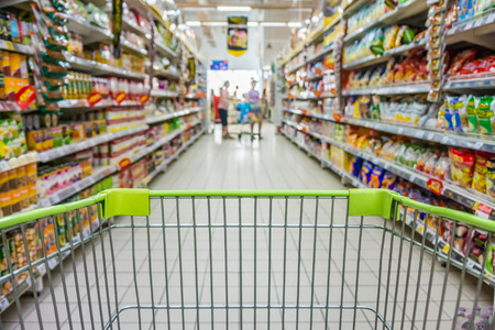 Foto de Shopping with shopping cart in snack department of supermarket - Imagen libre de derechos