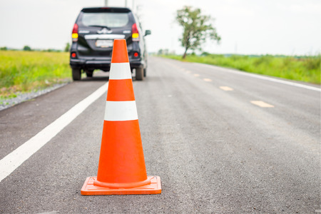 Foto de Orange traffic cone on country road. It is used for warning to broken down car on country road, Thailand. - Imagen libre de derechos