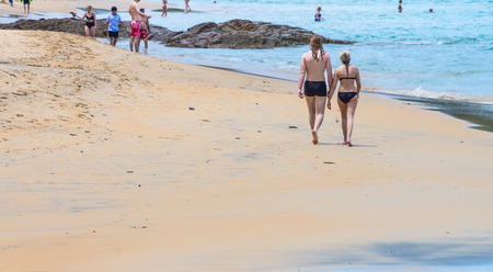 Photo for Couple in swimming suits walking on a beach. Tourist seaside attraction of Andaman sea in Thailand. - Royalty Free Image