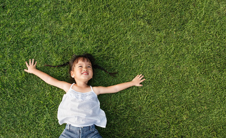 Photo for Asian little girl smile and lay on grass - Royalty Free Image