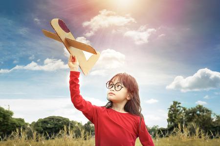 Foto de Little girl play paper plane with dreams of flight - Imagen libre de derechos