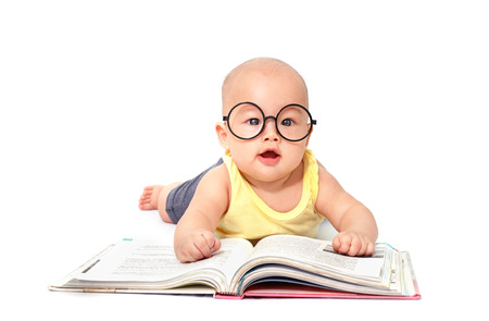 Photo pour Little baby crawl and reading a big book isolated on white background - image libre de droit