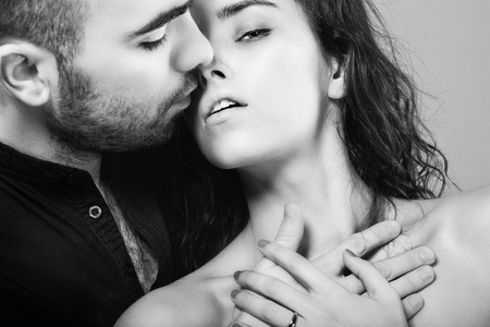 Photo for a hot man is kissing his  beautiful young woman - Royalty Free Image
