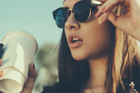 Photo for Pretty hipster girl in sunglasses with cup of coffee. Close-up lifestyle outdoor portrait - Royalty Free Image