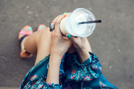 Photo pour Girl with glasses drinking milkshake. Outdoor lifestyle portrait of woman - image libre de droit