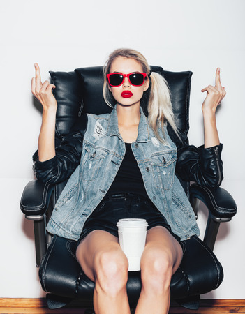 Foto de Young blonde woman in sunglasses sit on black office chair and showing middle finger and holding a cup of coffee knees . Fashoin hipster girl.  White background, not isolated - Imagen libre de derechos