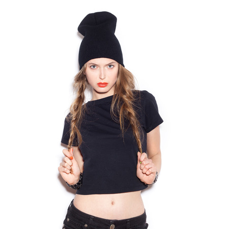 Foto de Fashion girl hipster hold by hands her two long braids. Woman in black clothes. White background, not isolated - Imagen libre de derechos