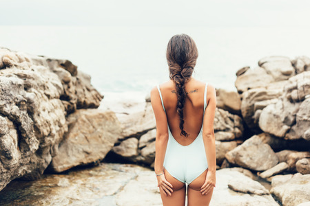 Photo pour Young woman in a swimsuit standing on the shore and  looking at the sea. Horizontal. Well being healthy lifestyle outdoor - image libre de droit