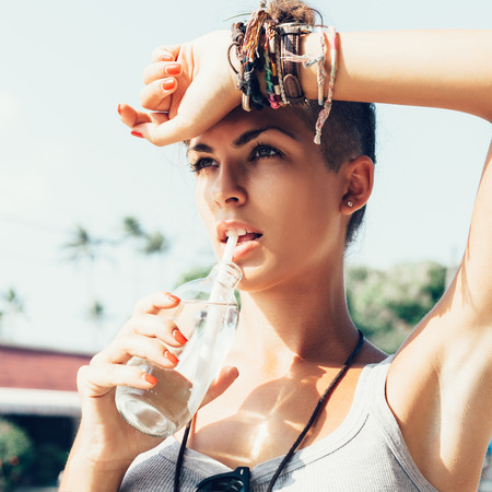 Photo for Portrait of young woman drinking water.  Stylish Girl against urban scene - Royalty Free Image