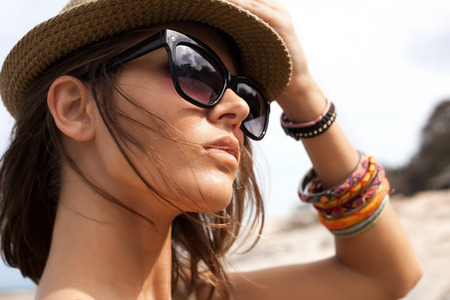 Photo pour Closeup of young summer sexy woman  wearing a hat  and sunglasses. Outdoors lifestyle portrait - image libre de droit