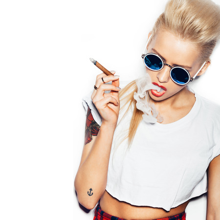 Foto de Sexy woman in sunglasses and white t-shirt blowing smoke from a cigar. Swag style girl. White background, not isolated - Imagen libre de derechos