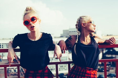 Photo pour portrait of two pretty hipster blonde sisters  wearing plaid skirt and black T-shirt - image libre de droit