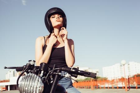 Photo pour Biker girl sits on vintage custom motorcycle and buttons helmet. Outdoor lifestyle portrait - image libre de droit