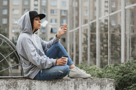 Foto de Outdoors lifestyle portrait os young woman sitting on the ground in the square, smoking a cigarette and drinking coffee from a paper cup. Hoodie, cap, jeans, snickers swag girl concept - Imagen libre de derechos