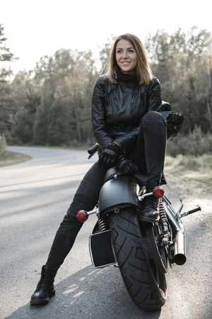 Foto de Young pretty cheerful woman sitting on motorcycle. Girl biker with perfect fit slim body and custom chopper motorbike at forest. Outdoor lifestyle portrait - Imagen libre de derechos