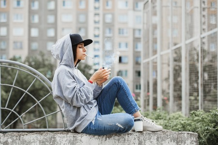 Foto de Sporty swag cool girl smoking cigarette and drinking coffee, sitting outside - Imagen libre de derechos