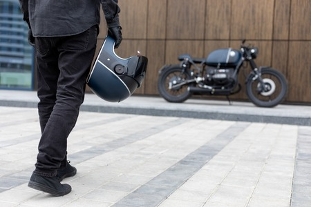 Photo pour Close-up of a handsome rider biker guy hand with black helmet in front of classic style cafe racer motorcycle. Bike custom made in vintage garage. Brutal fun urban lifestyle. Outdoor portrait. - image libre de droit