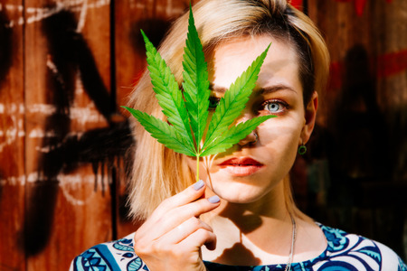 Foto de Beautiful girl with a cannabis leaf near the face - Imagen libre de derechos