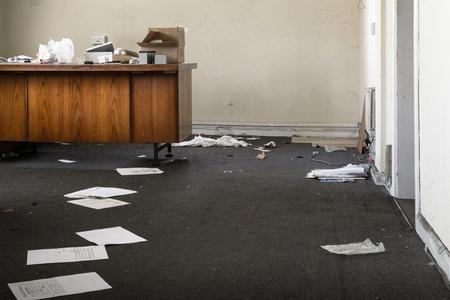 Foto de Abandoned Office with strewn discarded papers and rubbish on old wooden desks - Imagen libre de derechos