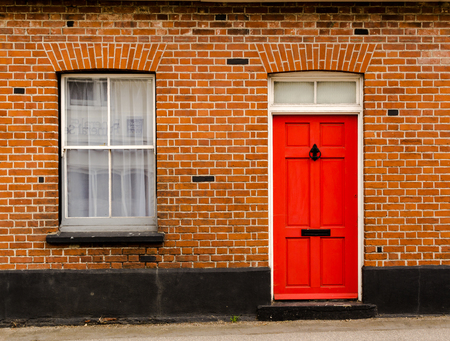 Photo for Single red painted wooden residential front door set in a traditional brickwork exterior with a window - Royalty Free Image