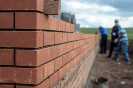 Foto de Newly built red brick wall of a newly built house with bricklayers in the background - Imagen libre de derechos