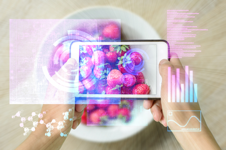Photo pour Woman holding a smart device uses reality augmentation to examine a pile of strawberries - image libre de droit