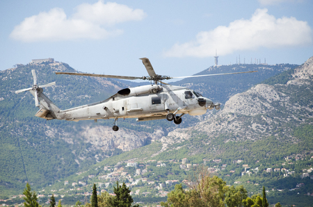 Foto de Black hawk helicopter approach landing, exhaust gas,  with aviation antennas on mountain background - Imagen libre de derechos