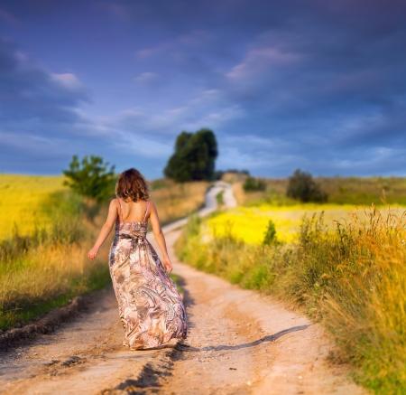 Beautiful white girl walking the road before sunset