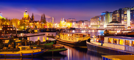 Photo pour Beautiful calm night view of Amsterdam city. Night time illuminations of buildings with reflections on water and boats in the canal. - image libre de droit