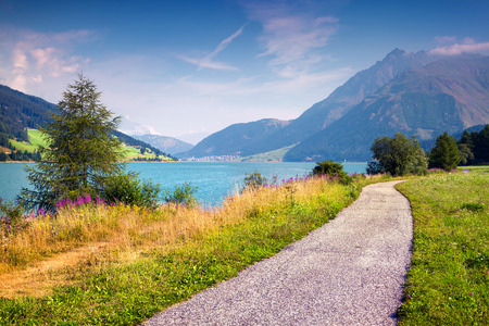 Bicycle path around Resia lake in the Italian Alps. Colorful summer morning on the Reschensee lake. Place is located near the village St. Valentin, Alps, Italy, Europe.