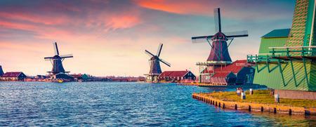 Foto de Panorama of authentic Zaandam mills on the water channel in Zaanstad village. Zaanse Schans Windmills and famous Netherlands canals, Europe. Instagram toning. - Imagen libre de derechos