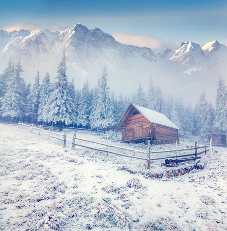 Foto de Old farm in the foggy winter mountains. - Imagen libre de derechos