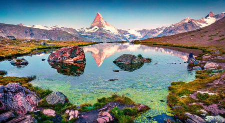 Foto de Colorful summer panorama of the Stellisee lake. Few minutes before sunrise. Great outdoor scene with Matterhorn (Monte Cervino, Mont Cervin) in Swiss Alps, Switzerland, Europe. - Imagen libre de derechos
