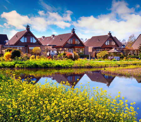 Foto de Sunny spting morning in with typical Holland building on the water canal. Beautiful outdoor scene in the Netherlands, Zaanstad village village location, Europe. Beauty of countryside concept background.  - Imagen libre de derechos