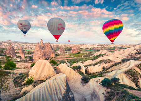 Foto de Flying on the balloons early morning in Cappadocia. Colorful spring sunrise in Red Rose valley, Goreme village location, Turkey, Asia. Traveling concept background. - Imagen libre de derechos