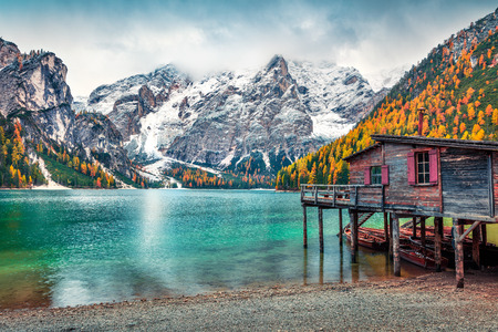 Foto de Boat hut on Braies Lake with Seekofel mount on background. Colorful autumn landscape in Italian Alps, Naturpark Fanes-Sennes-Prags, Dolomite, Italy, Europe. Traveling concept background. - Imagen libre de derechos