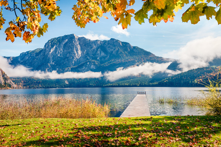 Foto de Bright autumn scene of Altausseer See lake. Sunny morning view of Altaussee village, district of Liezen in Styria, Austria. Beauty of countryside concept background. - Imagen libre de derechos