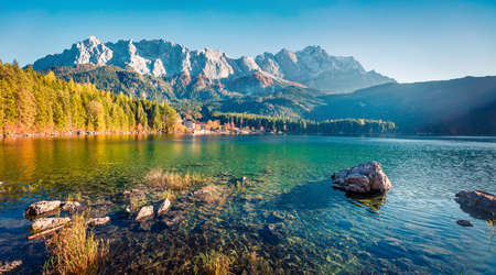 Foto de Sunny evening scene of Eibsee lake with Zugspitze mountain range on background. Beautifel autumn view of Bavarian Alps, Germany, Europe. Beauty of nature concept background. - Imagen libre de derechos