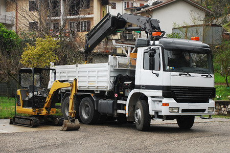 Foto de A compact mini hydraulic excavator with a rotating house platform and a truck-mounted  swing-arm crane. - Imagen libre de derechos