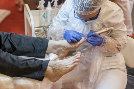Foto de The process of pedicure in a professional beauty salon. Toned image. hardware processing of toes. Care of the skin of the feet close up view - Imagen libre de derechos