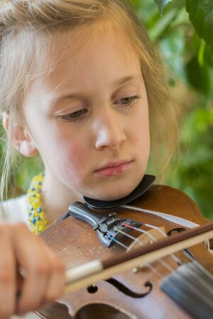 Photo pour Close up of a child playing violin on green background. Portrait of girl with string and playing violin. Portrait of the little violinist. Beautiful gifted little girl playing on violin. - image libre de droit