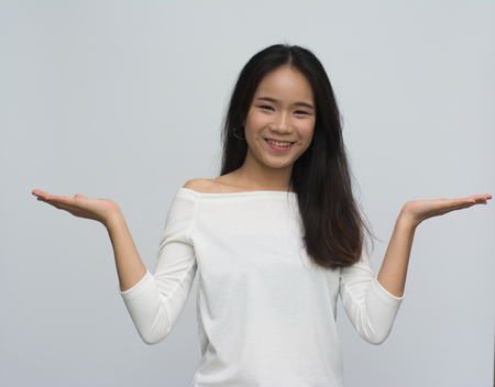 Foto de Asian girl shows a hand advertising. Woman with outstretched hand. Beautiful girl. Beautiful portrait of a girl in white shirt over a white background. - Imagen libre de derechos