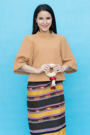 Foto de Portrait of asian young girl in traditional thai dress and holding jasmine garland isolated on blue sky background. Cotton dress - Imagen libre de derechos