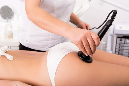 Photo for Woman getting anticellulite and anti fat therapy in beauty salon - Royalty Free Image
