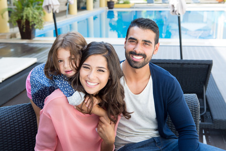 Photo pour Beautiful latin family relaxing close to the pool - image libre de droit