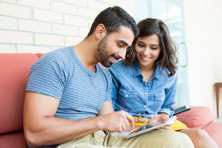 Foto de Fashion couple sitting together and using a tablet - Imagen libre de derechos