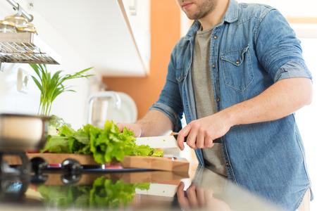 Foto de Man cooking and cutting veggies for lunch - Imagen libre de derechos