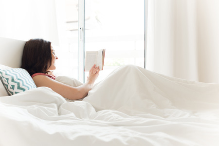 Photo pour Woman reading book in bed during the morning - image libre de droit